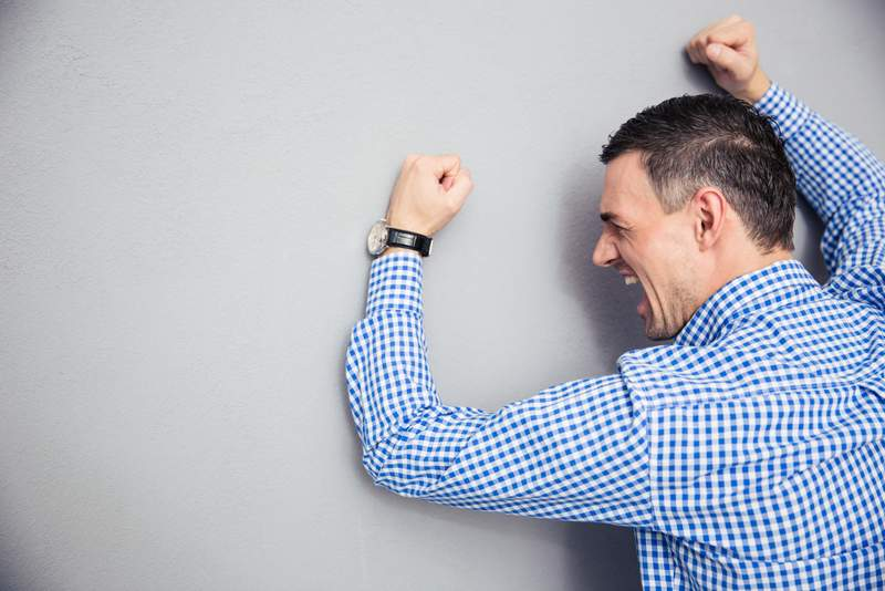 Angry man hitting wall